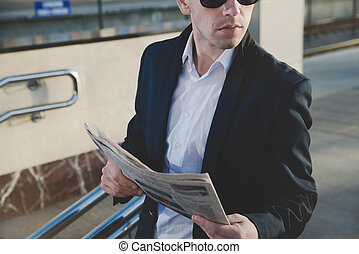 Businessman talking on the phone and holding a newspaper.