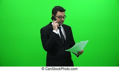 Businessman Talking On The Phone And Holding Papers On A Green Screen