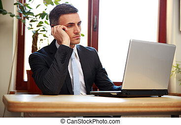 Businessman talking on the phone and using laptop in office
