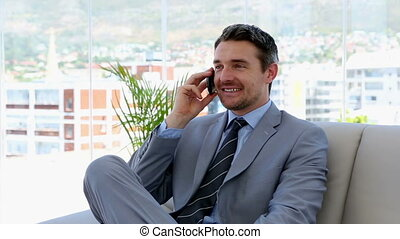 Businessman talking on the phone on the couch