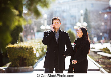businessman talking on the phone while woman comes to him