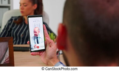 Disabled businessman talking on video call with doctor in work time sitting in wheelchair in modern company office using smartphone. Remotely medic advising freelancer using modern technology