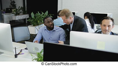 Businessman Talking To African American Male Colleague Explaining New Idea While Modern Business People Group Working On Computers In Open Office Space