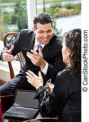 Businessman talking with female Hispanic coworker