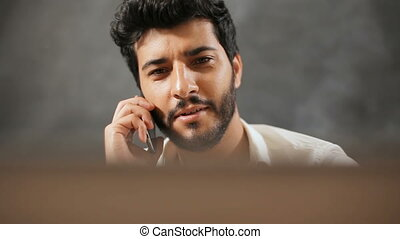 Businessman Talks on Phone before Laptop