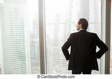 Businessman thinking about future near window