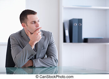 Businessman thinking and sitting behind a table