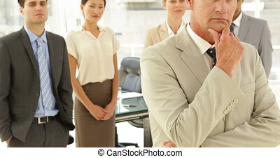 Businessman thinking in front of his staff