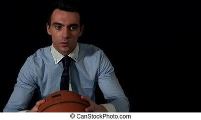 Businessman throwing basketball to camera on black...