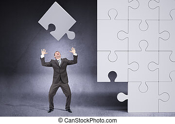 Businessman throwing on grey puzzle piece
