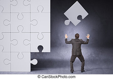 Businessman throwing on puzzle piece
