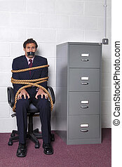 Businessman tied to an office chair with rope, look of fear on his face.