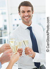 Businessman toasting with champagne in office