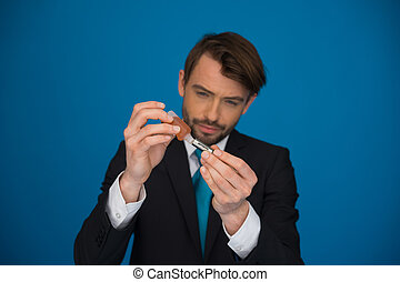 businessman topping up his e-cigarette with e-liquid on blue...