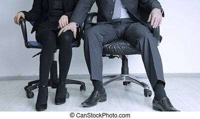 businessman touching leg of female colleague in office....