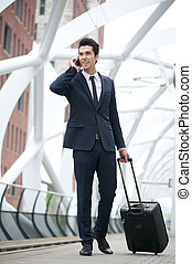 Businessman traveling and talking on phone at station