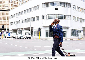 Businessman traveling with bag and talking on mobile phone