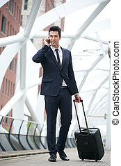 Businessman traveling with bag and talking on phone at station