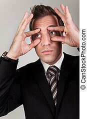 Businessman trying to stay awake by propping his eyes
