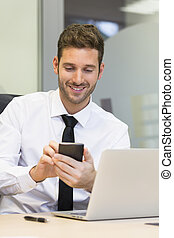 Businessman typing a message on mobile phone in office