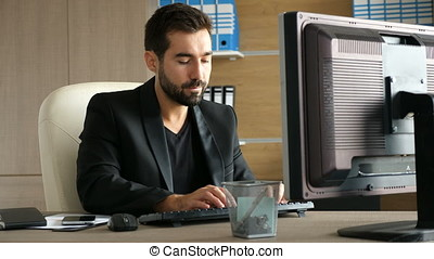 Businessman typing a reply on the computer while his phone is ringing