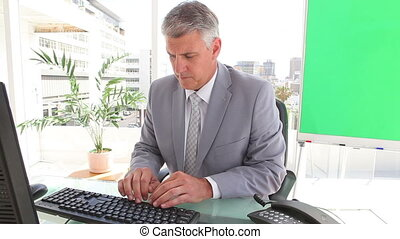 Businessman typing on a keyboard before looking at sheets