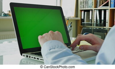 Businessman Typing on a Laptop. Man Answers the Call on His Smartphone. Device with Green Screen Display (Chroma Key) 4K