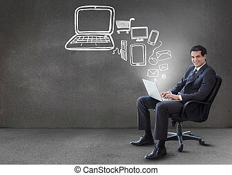 Businessman typing on his laptop with media device graphics coming from it in grey empty room