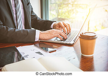Businessman typing on laptop computer in office