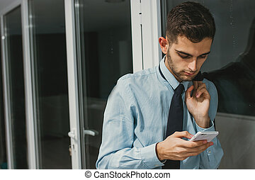 businessman typing on the mobile phone in the office