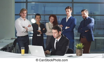 Businessman under stress at work. Colleagues are standing behind and watching.