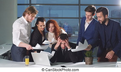 Businessman under stress at work. Colleagues shaking papers in his face.