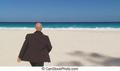 businessman undressing on beach