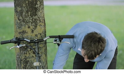 Businessman unlock bicycle from a tree - Young businessman ...