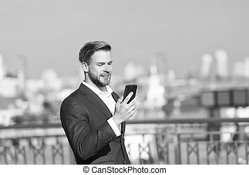 Businessman use smartphone with smile. Happy man with mobile phone on sunny terrace. Great business news. Communication and agile business. Business communication. New technology and modern life