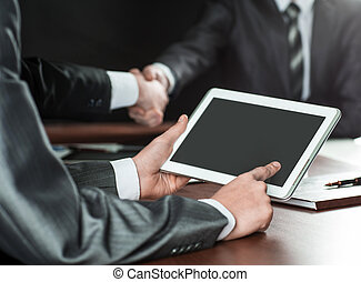 businessman uses a digital tablet at a briefing in the office