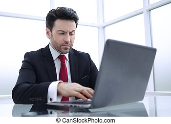businessman uses a laptop for work.