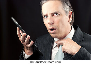 Businessman Uses Tablet, Looks To Camera Concerned