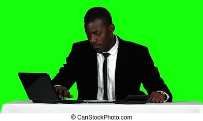 Businessman uses the calculator and a laptop. Green screen