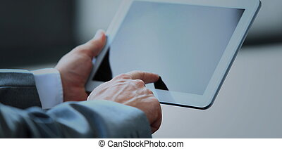 Businessman uses the tablet in a modern office