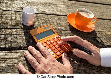 Businessman using a colorful orange manual calculator