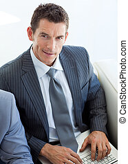 Businessman using a laptop and sitting in a waiting room