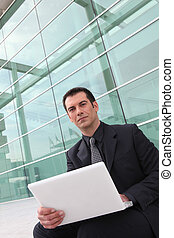 Businessman using a laptop outside a glass building