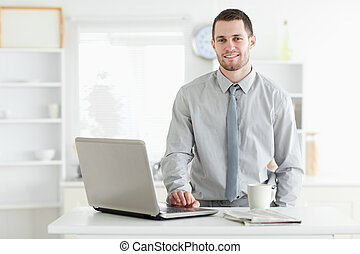 Businessman using a laptop while drinking tea