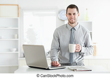 Businessman using a notebook while drinking coffee