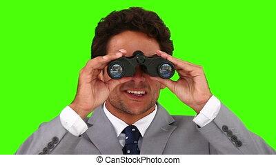 Chromakey footage of a businessman using a pair of binoculars