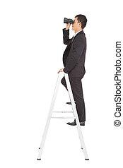 businessman using a pair of binoculars standing  on stair