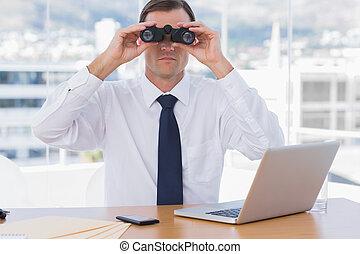 Businessman using binoculars in his office