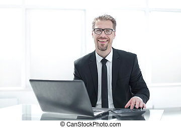 Businessman using calculator on office desktop with laptop