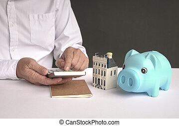 Businessman using calculator with a model house and piggy bank on table.